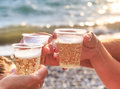 Three friends at the beach are drinking sparkling wine at sunset Royalty Free Stock Photo