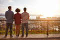 Three friends on a bridge looking out Royalty Free Stock Photo