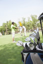 Three friends playing golf on the golf course, focus on the  caddy Royalty Free Stock Photo