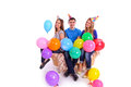 Three friends sitting on a couch with balloons and hats Royalty Free Stock Photo
