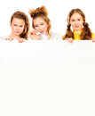 Three friends smiling girls standing together and hold white board isolated over white Royalty Free Stock Photo
