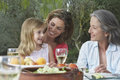 Three generation family at garden table grandmother mother and daughter sitting in Stock Images