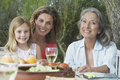 Three generation family at garden table portrait of grandmother mother and daughter sitting in Royalty Free Stock Photography