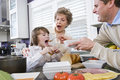 Three generation family in kitchen eating lunch Stock Photo