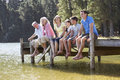 Three Generation Family Sitting On Wooden Jetty Looking Out Over Royalty Free Stock Photo