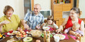 Three generations family at table in home drinking and eating Royalty Free Stock Photography