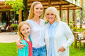 Three generations of happy women family bonding to each other and smiling while standing in front their house Royalty Free Stock Photo