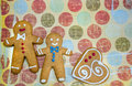 Three gingerbread cookie men on fancy background with a heart Royalty Free Stock Image