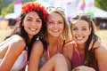 Three girl friends at a music festival looking to camera Royalty Free Stock Photo