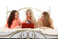Three girlfriends with laptop beautiful cheerful lie on a bed on a white background Royalty Free Stock Photography