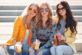 Three girlfriends sitting on steps in park beautiful young women two blondes and a brunette the drinking fruit juice and wearing Royalty Free Stock Photos