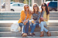 Three girlfriends sitting on steps in park beautiful young women two blondes and a brunette the drinking fruit juice and wearing Royalty Free Stock Photo