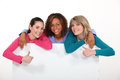 Three girls behind white panel Stock Photos