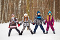 Three girls and boy stand holding hands and legs spread wide one in winter park Royalty Free Stock Photo