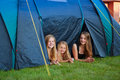 Three girls camping looking out of their tent Stock Photos
