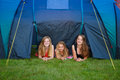 Three girls camping looking out of their tent Stock Images