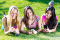 Three girls chatting with their smartphones at the park Stock Images