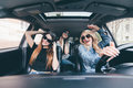 Three girls driving in a convertible car and having fun, listen music and dance Royalty Free Stock Photo