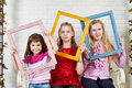 Three girls with frames of paintings posing in the studio Royalty Free Stock Photos