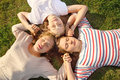 Three girls hold hands and lie on grass. Royalty Free Stock Photo