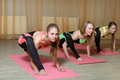 Three girls in identical costumes perform exercises yoga classes on mats the sports room Stock Photography
