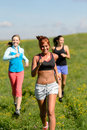 Three girls jogging downhill summer meadow and smiling Stock Photo