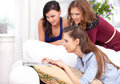 Three girls and a laptop in liveroom Royalty Free Stock Images