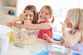Three girls making cupcakes in kitchen being messy Royalty Free Stock Photos