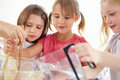Three girls making cupcakes in kitchen close up of Royalty Free Stock Photography