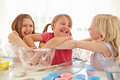 Three girls making cupcakes in kitchen having fun Stock Photography
