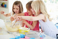 Three girls making cupcakes in kitchen having fun Royalty Free Stock Images