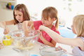 Three girls making cupcakes in kitchen helping each other Stock Photo