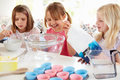 Three girls making cupcakes in kitchen at home having fun Stock Images