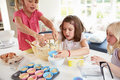 Three girls making cupcakes in kitchen at home having fun Royalty Free Stock Photography