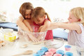 Three girls making cupcakes in kitchen putting hands into glass bowl Stock Image