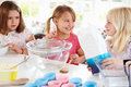 Three girls making cupcakes in kitchen smiling at each other Stock Photos