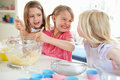 Three girls making cupcakes in kitchen smiling at each other Royalty Free Stock Photos