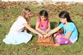 Three girls playing chess smiling barefoot kids sitting on the grass and game Royalty Free Stock Image