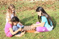 Three girls playing dice smiling barefoot kids sitting on the grass and game with dices Royalty Free Stock Image