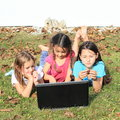 Three girls playing with notebook smiling barefoot kids lying on the grass and a computer Royalty Free Stock Photography