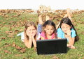 Three girls playing with notebook smiling barefoot kids lying on the grass and a computer Stock Photos