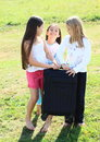 Three girls prepared for traveling with suitcase barefoot packed chech in baggage Stock Photo