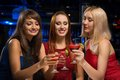 Three girls raised their glasses in a nightclub have fun with friends Stock Images
