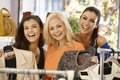 Three girls shopping together clothes store smiling happy looking camera Royalty Free Stock Photos