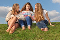 Three girls sit at grass, chat and laugh Royalty Free Stock Photo