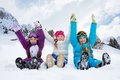 Three girls on snow day group of kids sitting in together holding hands Stock Photo