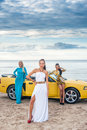 Three girls with sport car on a beach Stock Image