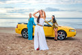 Three girls with sport car on a beach Stock Photos