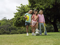 Three girls standing on grass in park with frisbee soccer ball and skipping rope portrait Stock Images