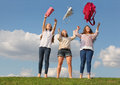 Three girls throw up bags and stand at grass Royalty Free Stock Photography